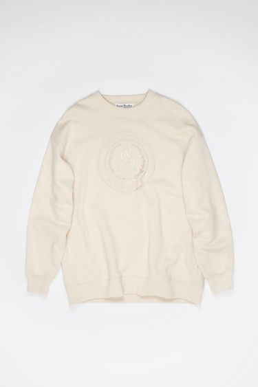 Acne Studios coconut white oversized sweatshirt is made of cotton with an embroidered logo design on the front.