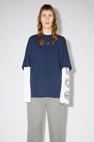 Acne Studios navy relaxed fit t-shirt is made of cotton jersey and features the layered look of a short and long sleeved t-shirt.