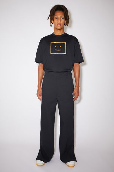 Acne Studios black wide leg track pants are made of structured fabric with a reflective face logo under one front welt pocket.