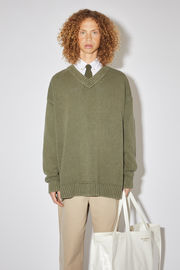Acne Studios dusty green v-neck sweater is made of a cotton blend with ribbed accents, washed for a distressed look.