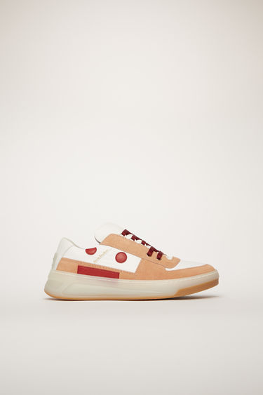 Acne Studios Steffey Lace Up Embr pink/white/ice sneakers are crafted from a mix of nylon, suede, and leather and features a face motif stitched on the side panel.