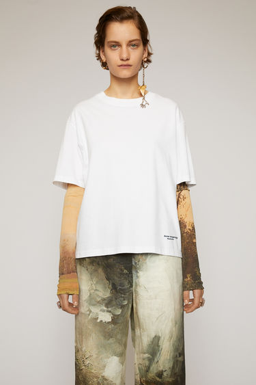 Acne Studios optic white t-shirt is cut to an oversized fit from cotton jersey with a stepped hemline and features a contrasting tape that's purposefully applied with irregular folds.