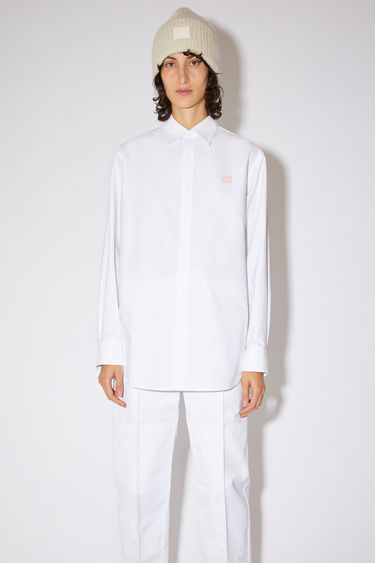 Acne Studios white button down Oxford shirt is made of cotton with a face logo patch at the chest.