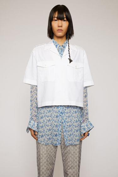 Acne Studios white safari shirt is crafted from cotton-poplin to a cropped, boxy silhouette and features traditional details, including a cuban collar, epaulettes, and utilitarian flap pockets.