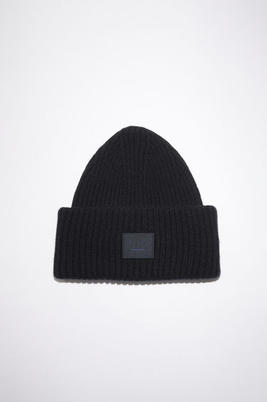 Acne Studios black beanie hat is made from rib knit wool with a face logo patch.