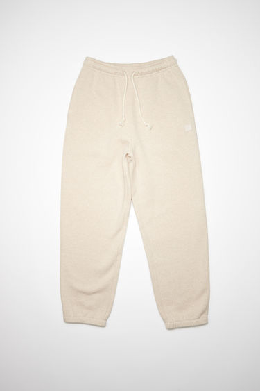 Acne Studios oatmeal beige organic cotton sweatpants feature an elastic drawstring waist and tonal embroidered face patch on the front.