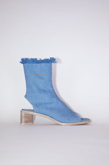 Acne Studios blue/ecru open toe and heel sandals are made of denim with a fringed top.