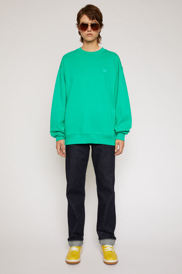 Acne Studios emerald green sweatshirt is crafted from midweight loopback fleece to a loose silhouette and finished with a face-embroidered patch on the chest.