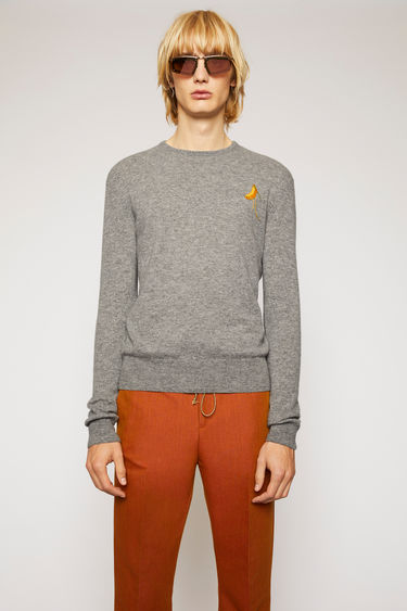 Acne Studios grey melange sweater is knitted with a fine gauge from soft lamb wool yarns and features a fruit patch that's left with loose hanging threads.