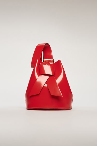 Acne Studios Musubi red bucket bag features a twisted knot inspired by the formation of traditional Japanese obi sash. It's crafted from high-shine leather and has a detachable zip pouch to store small essentials.