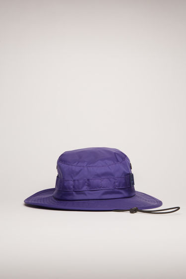 Acne Studios sea blue nylon bucket hat is crafted with a flat-topped crown and quilted brim and features metal eyelet vents, elastic drawstring and a face-embroidered patch.