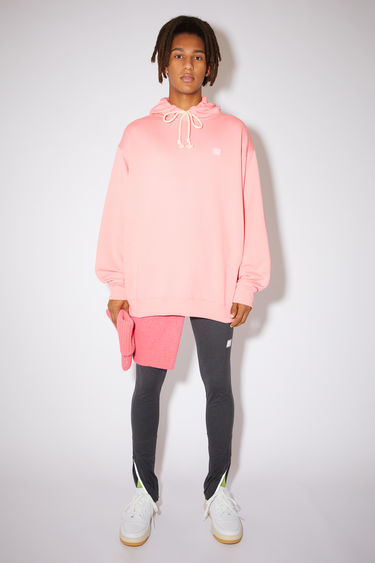 Acne Studios blush pink oversized hooded sweatshirt is made of organic cotton with a face logo patch and ribbed details.