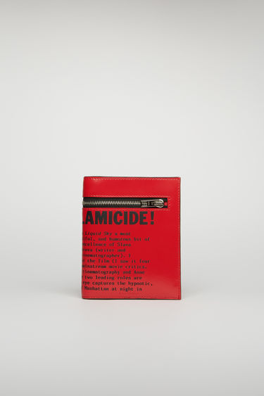 Acne Studios red/black trifold wallet is crafted from high-shine leather and features an excerpt from the Propaganda Magazine across the front. Secured with metal zip closure, the accessory holds space for cards, notes and coins.