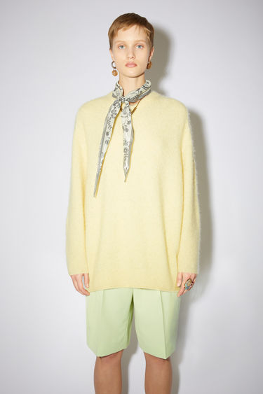 Acne Studios pale yellow soft, luxurious v-neck sweater is made of a fluffy alpaca blend with fully fashioned details.