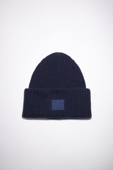 Acne Studios navy oversized beanie is knitted in a thick rib-stitch from soft wool and features a tonal face-embroidered patch.