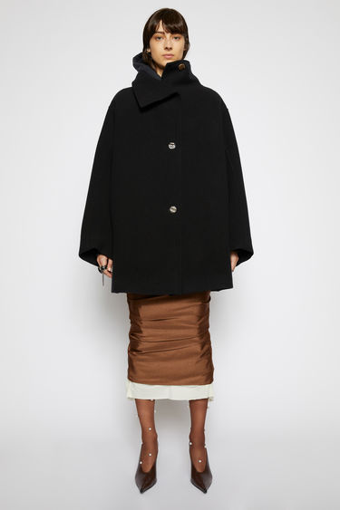 Acne Studios black coat is crafted from boiled wool to an oversized, A-line silhouette with a wide funnel neckline and sleeves and adorned with tonal ceramic buttons.