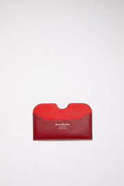 Acne Studios burgundy multi colour block card holder is made of soft grained leather with a silver logo stamp.