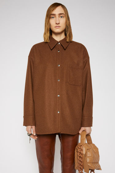 Acne Studios cognac brown flannel overshirt is cut generously through the body with dropped shoulders and crafted with a neat, point collar, front patch pocket and silver snap buttons.