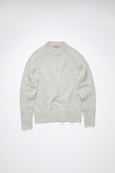Acne Studios light grey melange crew neck sweater is made of Shetland wool with an embroidered logo at the chest.