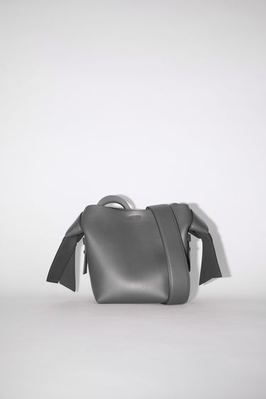 Acne Studios dark grey small bag features twisted knots inspired by traditional Japanese obi sashes. It has a debossed logo and snap button closure, which opens to reveal a zipper compartment for storing small essentials.