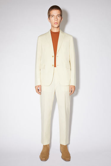 Acne Studios champagne beige single-breasted suit jacket is made of cotton and features a classic fit.