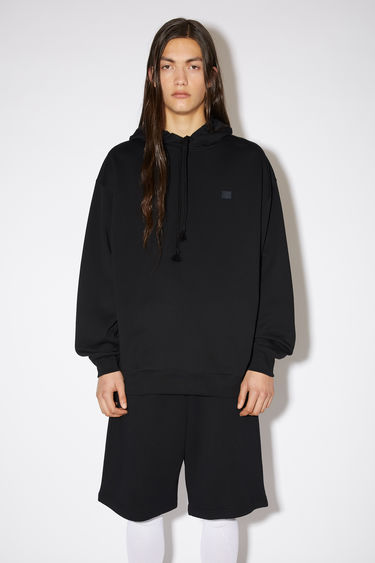 Acne Studios black hooded sweatshirt is crafted from midweight loopback fleece to an oversized fit and finished with a tonal face patch on the chest.