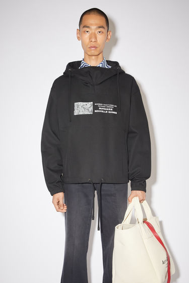 Acne Studios black hooded anorak jacket is made of a cotton blend with a front print, in collaboration with Dizonord, a record store in Paris, France.
