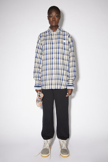 Acne Studios oat beige/blue relaxed button down shirt is made of organic cotton flannel with a face patch at the chest.