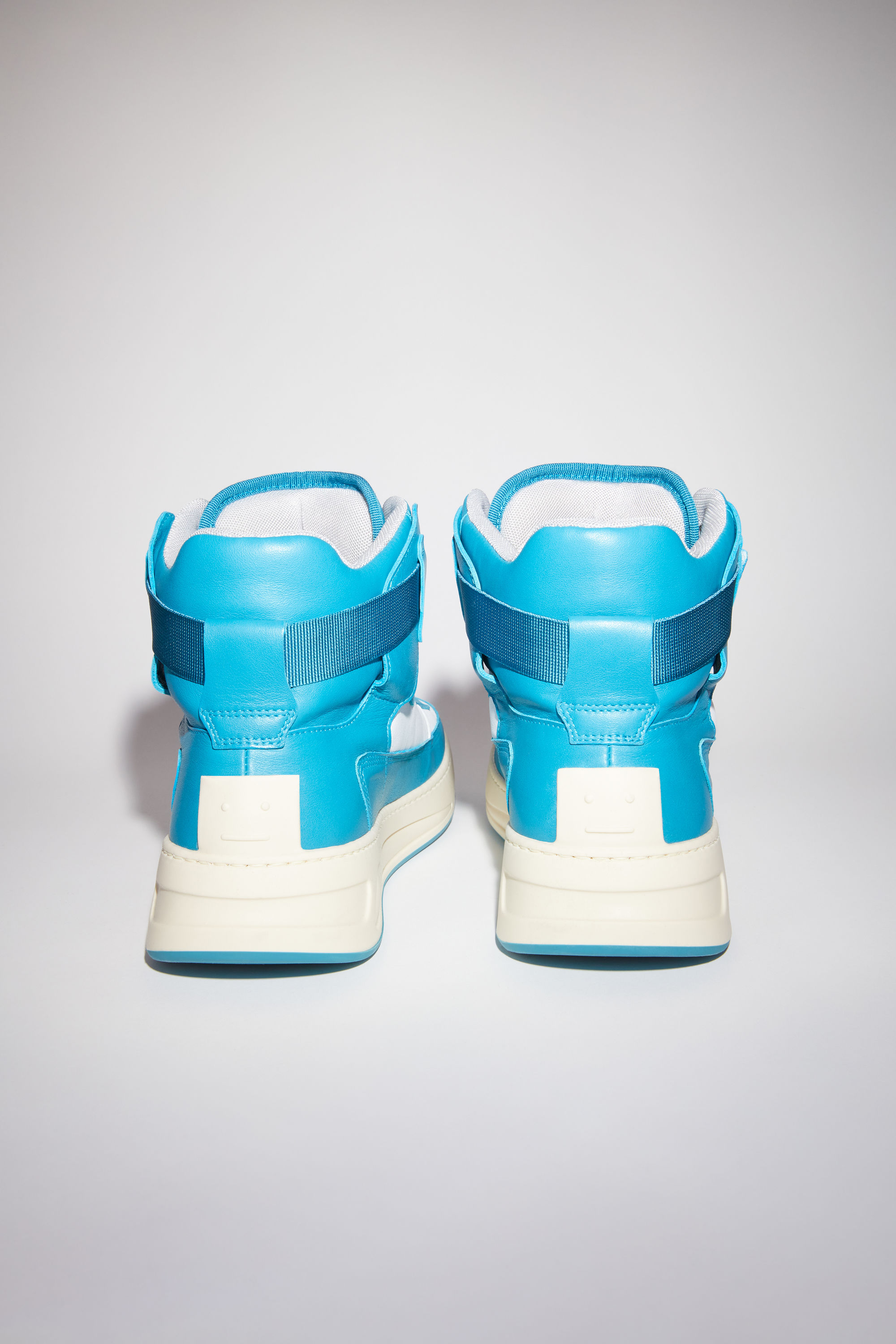 Acne Studios turquoise/white/white lace-up high top sneakers are made of calf leather with a face motif on the back sole. 003