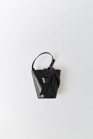 Acne Studios Musubi Bucket black is made from smooth leather and features a neat knot detail based on the Japanese obi sash.