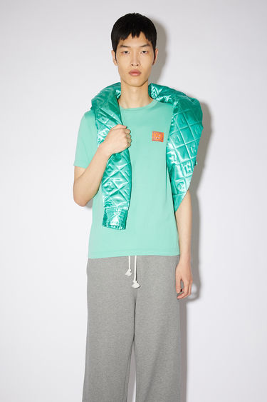 Acne Studios jade green cotton jersey t-shirt features a contrasting beaded face patch at the chest.