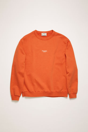 Acne Studios poppy red sweatshirt is made from cotton jersey that has been garment dyed for a soft, washed-out finish and it features a reversed logo printed across the chest.