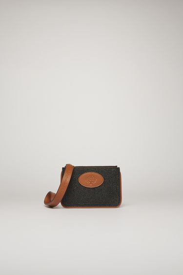Acne Studios launches a collection of bags and accessories with Mulberry. The Coin Purse Scotch grain is accented with a co-branded leather zip puller and framed with brown leather piping.