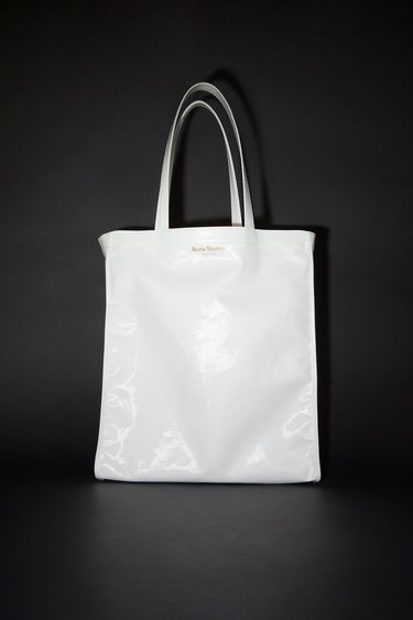 Acne Studios white oilcloth tote bag features Acne Studios branding.
