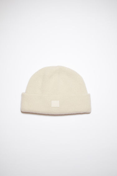 Acne Studios cream beige beanie is knitted with wool and lycra for a closer fit and accented with a small tonal face-embroidered patch on the turn-up.