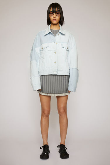 Acne Studios light blue jacket is handcrafted in a patchwork pattern from deadstock denim and finished with raw edges along the seams. It's cut in a boxy silhouette with dropped shoulders and finished with buttoned patch pockets.