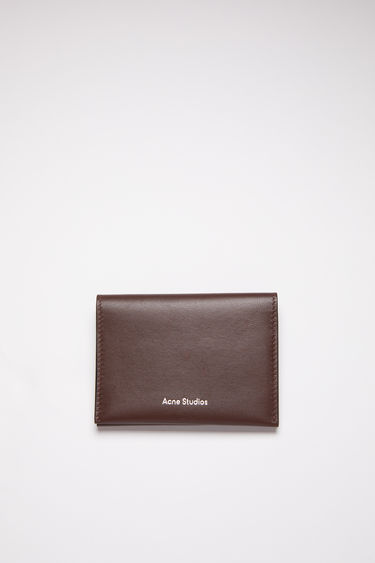 Acne Studios dark brown bifold card holder is made of soft grained leather with four card slots and a silver stamped logo on the front.