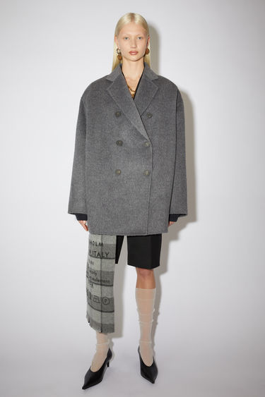 Acne Studios grey melange double-breasted coat is tailored from a brushed wool and alpaca blend to a relaxed silhouette with dropped shoulder seams and notch lapels.