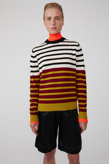 Acne Studios launches an exclusive range with Swedish artist Jacob Dahlgren. As part of the collaboration, the burgundy multi sweater is finely knitted from wool and patterned with horizontal stripes.