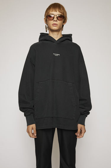 Acne Studios black hooded sweatshirt is made from brushed cotton jersey that's been garment dyed for a soft, washed-out finish and features a reversed logo purposely printed imprecisely across the front.