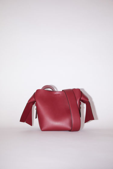 Acne Studios Musubi Mini burgundy bag features twisted knots inspired by traditional Japanese obi sashes. It's crafted with a top handle and detachable shoulder strap and has a press-stud fastening which opens to reveal a leather-lined interior with a zipped divider.