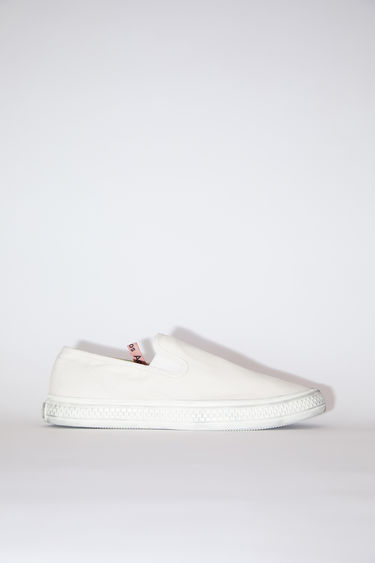 Acne Studios off white/off white distressed canvas slip-on sneakers have rubber soles.