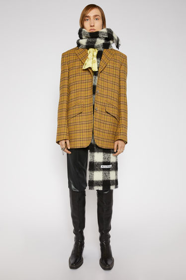 Acne Studios yellow/beige checked suit jacket is crafted to a boxy silhouette with lightly padded shoulders and notch lapels and features slanted flap pockets and elbow patches.