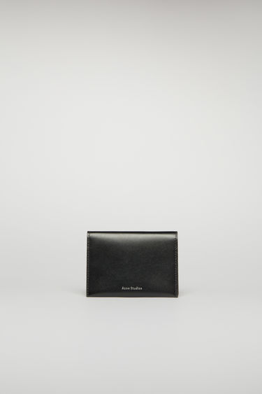 Acne Studios black bifold cardholder is crafted from smooth leather and features four card slots and a silver stamped logo on the front.