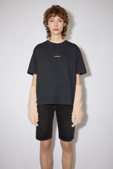 Acne Studios black t-shirt is made from pigment-dyed jersey that's lightly faded along the seams. It's cut to a relaxed silhouette with dropped shoulders and features a raised logo print on front.