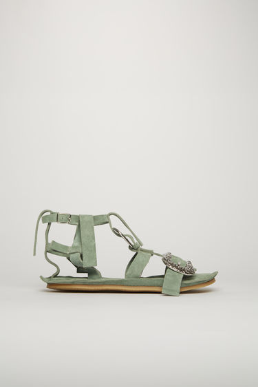 Acne Studios pastel green sandals are crafted with slim suede straps across the front and accented with silver-tone metal buckles.