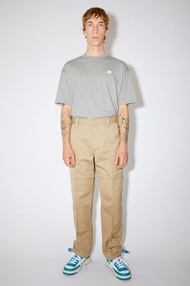 Acne Studios beige classic workwear trousers are made of a cotton twill blend with creased legs and a leather face patch.