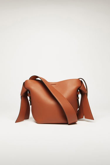 Acne Studios Musubi Mini almond brown bag features twisted knots inspired by the formation of traditional Japanese obi sash. It's crafted from soft grain leather and has a central zipped divider to store small essentials.