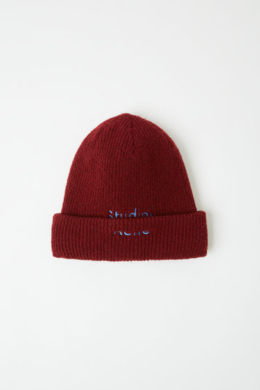 Acne Studios rosewood red beanie is crafted from a ribbed wool-blend with a turn up hem and embroidered with a broken logo.