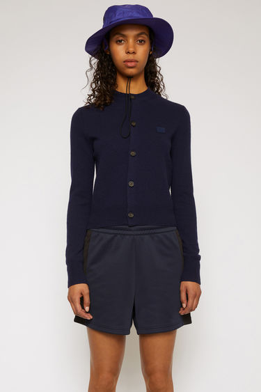 Acne Studios navy blue cardigan is knitted in a fine gauge from soft wool yarns and accented with a tonal face-embroidered patch on the chest.